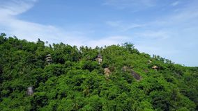 Aerial view of private secluded villas on tropical island in remote location among green palm trees. Shot with a DJI Mavic fps29,97 4k stock video footage