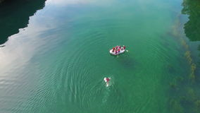Aerial view of rafter swimming to boat after falling from it stock video