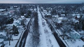 Aerial view of railroad tracks in a small town covered in snow on a cold winter day