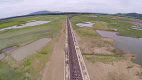 Aerial view railroad for train crossing bridge on dam,Beside a mountain forest and water resources,Thailand stock video