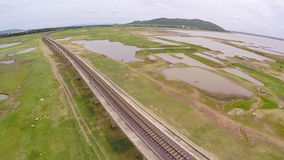 Aerial view railroad for train crossing bridge on dam,Beside a mountain forest and water resources,Thailand stock footage