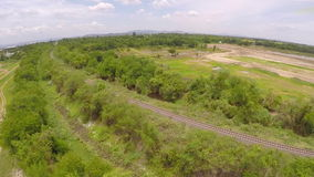 Aerial view railroad for train crossing bridge on dam,Beside a mountain forest and water resources,Thailand. Video shot from a drone show aerial view of train stock footage