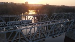 View from the height of the railway bridge on which the train is passing at sunset. Aerial view of the railway bridge on which the train is passing at sunset stock footage
