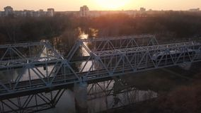 View from the height of the railway bridge on which the train is passing at sunset. Aerial view of the railway bridge on which the train is passing at sunset stock video footage