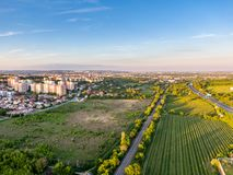 Aerial view of railway during sunset. City panorama in the background. Trees, grass and bushes in the foreground.  royalty free stock images