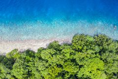 Aerial View of Rainforest and Reef in Papua New Guinea. Aerial view of reef and rainforest in Papua New Guinea. The remote, tropical islands in this region are stock photo