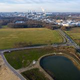 Aerial view of a rainwater retention basin with roads and a large meadow area and an industrial city in the background. Aerial view of a rainwater retention stock image