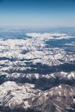 Aerial View of Snowy Mountain Range. An aerial view of range of snow-capped mountains with blue sky in the background Stock Photo