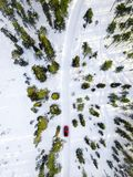 Aerial view of red car driving through the white snow winter forest on country road in Finland, Lapland stock photography