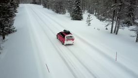 Aerial view of the only red car on the road in the beautiful winter landscape of Lapland after a snowfall. Close-up tracking of the car at high speed. Aerial stock footage