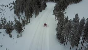 Aerial view of the red car on the road in the beautiful winter landscape of Lapland during a snowfall. Linear tracking of the car. Aerial 4K video stock footage