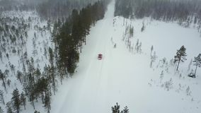 Aerial view of the only red car on the road in the beautiful winter landscape of Lapland during a snowfall. Linear tracking of the car. Aerial 4K video stock footage