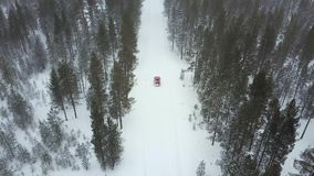Aerial view of the only red car on the road in the beautiful winter landscape of Lapland during a snowfall. Tracking a retiring car. Aerial 4K video stock footage