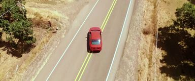 Aerial view, red car turns off the road stock image