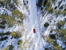 Aerial view of a red car on white winter road. Winter landscape countryside. Aerial photography of snowy forest with a car on the Royalty Free Stock Photos