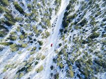 Aerial view of a red car on white winter road. Winter landscape countryside. Aerial photography of snowy forest with a car on the Royalty Free Stock Images