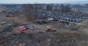 Aerial view of red fire truck with led light. Burning dump. Aerial view from drone of dense smoke poured in air and red fire-truck on fireground stock video footage