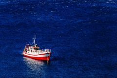Aerial view of red fishing boat on a deep blue sea in Greece. Aerial view of red fishing boat on a deep blue sea in harbor. Greece royalty free stock photo