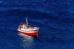 Aerial view of red fishing boat on a deep blue sea in Greece. Aerial view of red fishing boat on a deep blue sea in harbor. Greece stock photography
