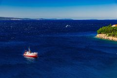 Aerial view of red fishing boat on a deep blue sea in Greece. Aerial view of red fishing boat on a deep blue sea in harbor. Greece royalty free stock image