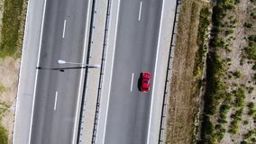 Aerial view of a red retro car drive on road or highway in the middle of the day. Not a lot of cars on motorway. stock video