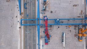 Aerial view of red and yellow lifting cranes installed near the railway in the industrial zone. Clip. Construction and stock footage