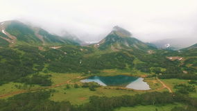 Aerial View. Reflections of the mountain in a lake. Close approach to waterfall by dron. stock footage