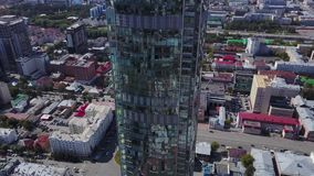 Aerial view of reflective office skyscrapers and traffic jam in a modern financial district. Mirrors of sky and. Cityscape on evening time with curve of glass stock footage
