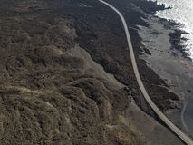 Aerial view of reliefs, volcanoes and lava fields in Lanzarote island, Canary Islands, Spain. Rugged coastline and road that runs along the sea royalty free stock photo