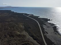 Aerial view of reliefs, volcanoes and lava fields in Lanzarote island, Canary Islands, Spain. Rugged coastline and road that runs along the sea stock photo