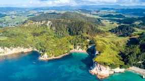 Aerial view on a remote ocean coast with small coves and mountains on the background. Coromandel, New Zealand. Coromandel peninsula is popular tourist Royalty Free Stock Images