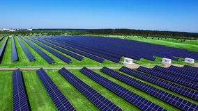 Aerial view of renewable electric power station with industrial solar panels. Drone view on photovoltaic panels of large solar farm on green field. Sun energy stock footage