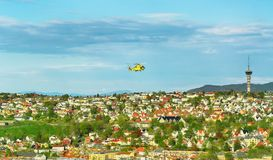 Aerial view of Trondheim with air ambulance helicopter. Aerial view of the residential district , TV tower and flying air ambulance helicopter in the norwegian royalty free stock photo