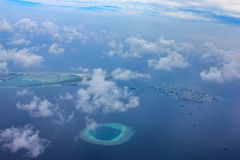 Aerial view of resort island and Male city airport in Maldives located in Indian ocean near topical atoll under clouds stock photos