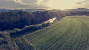Aerial view of river bending across fields at sunset. Stock Photo
