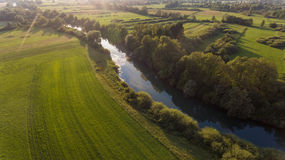 Aerial view of river bending across fields at sunset. Royalty Free Stock Photo