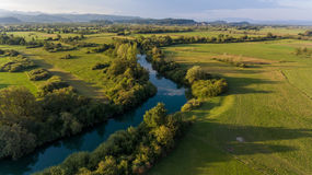 Aerial view of river bending across fields at sunset. Royalty Free Stock Photography
