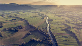 Aerial view of river bending across fields at sunset. Royalty Free Stock Photos