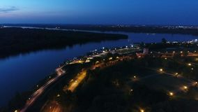 Aerial view of a river bank and city outskirt in night stock video footage