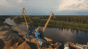 Aerial view:River port with cranes and ships. Aerial:port cargo cranes and ship fragment at the docks.Aerial view:Container cranes in cargo port terminal, cargo stock video