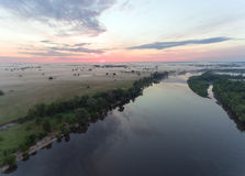 Aerial view of river at sunrise, fly over morning mist on the river Royalty Free Stock Image