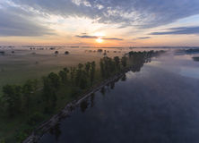 Aerial view of river at sunrise, fly over morning mist on the river Royalty Free Stock Photo