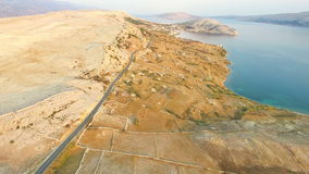 Aerial view of road through barren landscape of Pag island in Croatia. Aerial view of road through barren landscape of Pag island in Dalmatia,Croatia stock footage