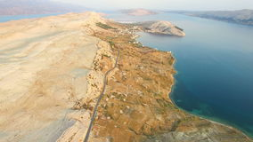 Aerial view of road through barren landscape of Pag island in Croatia. Aerial view of road through barren landscape of Pag island in Dalmatia,Croatia stock video footage