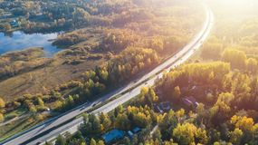 Aerial view of road in beautiful autumn forest. Beautiful landscape with asphalt rural road, trees with red and orange leaves. Highway through the park. Top royalty free stock images