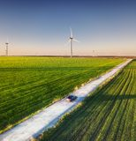 Aerial view of road on beautiful summer field at sunset. Landscape with rural road, wind power turbines. Road through the field. T. Op view from flying drone stock photo