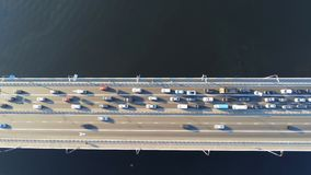 Aerial view of road bridge across river with heavy traffic jam in one direction. Rush hour with mash and overloading of. Road infrastructure. Resolving of car stock footage