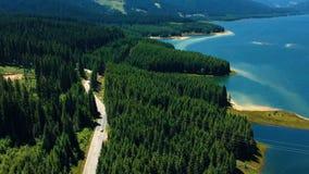 Aerial view of Oasa lake, on Transalpina mountain road. Aerial view of a road crossing Oasa lake, near Transalpina and Sibiu, Romania stock video footage