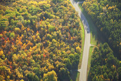 Aerial view of road curving through woods in fall color Royalty Free Stock Images