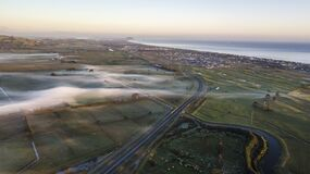 Aerial view on the road and fields with morning mist